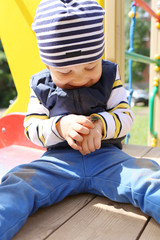 lovely baby with beetle on playground