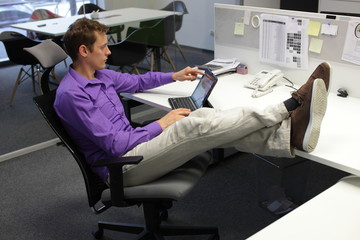 business man in relaxed sitting position with legs on desk