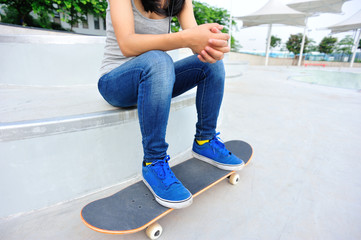 woman skateboarder sit at skatepark