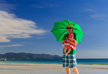 father and daughter with umbrella on the beach