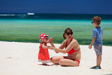 mother with kids playing on tropical beach