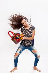 Модная девушка с сумкой в руках и кудрявыми волосами