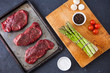 Three raw filet steaks with green asparagus