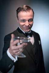 Smiling retro 1920 business fashion man holding champagne glass.