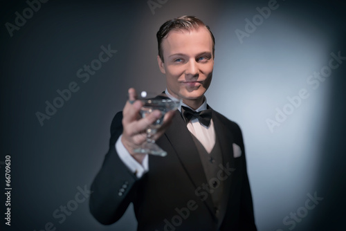 Smiling retro 1920 business fashion man holding champagne glass. - 66709630