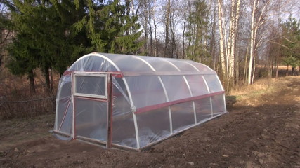 new plastic greenhouse hothouse in spring garden
