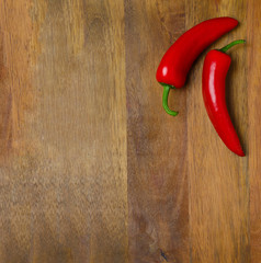 two red hot chili peppers on a wooden background