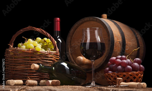 Still life with wine bottles, glasses and oak barrels