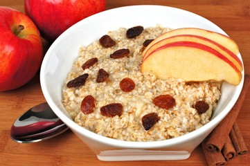 Bowl of breakfast oatmeal with apples, raisins and cinnamon