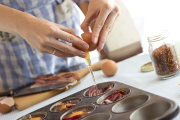 Woman cracking an egg into a muffin pan