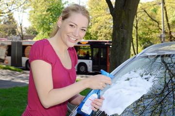 Frau putzt Windschutzscheibe mit Fensterspray