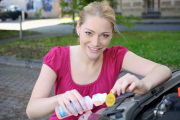 Frau füllt Scheibenreiniger in Auto
