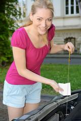 Frau kontrolliert Ölstand mit Peilstab