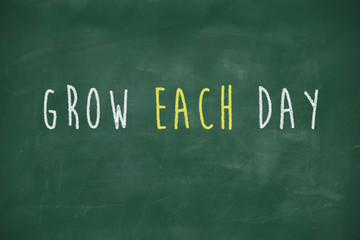 Grow each day handwritten on blackboard