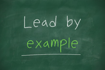 Lead by example handwritten on blackboard