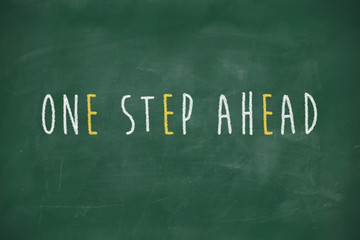 One step ahead handwritten on blackboard