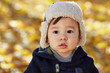 Closeup portrait of little boy in jacket and fur cap