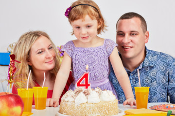 Happy family of three sits at birthday table