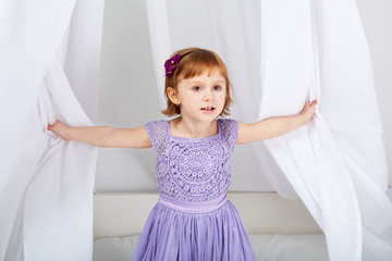 Little girl dressed in holiday clothes looks out from under tent
