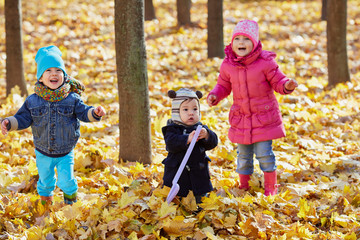Children stand and laugh in autumn park
