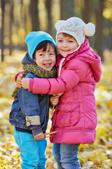 Smiling little girl hugs younger boy in autumn park