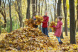 Mother and children gather fallen leaves in one big heap