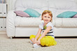 Smiling little girl sits on light carpet in room