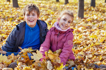 boy and girl sit on ground in drift of fallen maple leafes