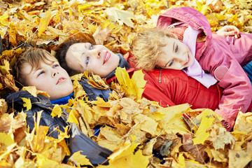 Mother and children lie in autumn park in drift