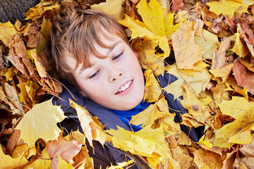 portrait of boy who lies on ground strewn