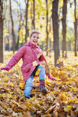 Little girl runs along autumn park kicking up fallen leaves