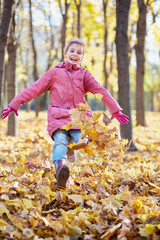 girl runs along autumn park and kicks up fallen leaves