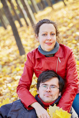 Woman sits on fallen leaves in autumn park and man head lies