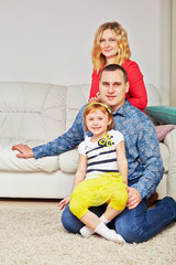 Family of three sits on carpet and on soft in light room
