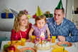 Family of three sits at birthday table