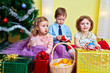 Three children sit in room under christmas tree with gift boxes