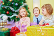 Three children sit in room under christmas tree with gift boxes,