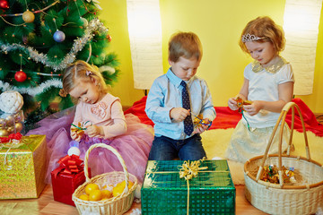 Three children sit in room under christmas tree among gift boxes