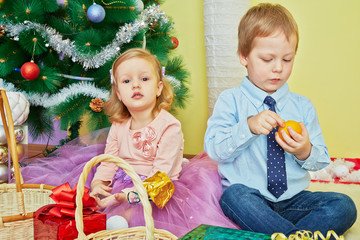 Little girl and boy sit on furry rug under christmas tree