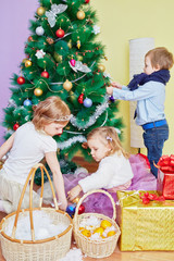 Little boy and two little girls decorate christmas tree in room