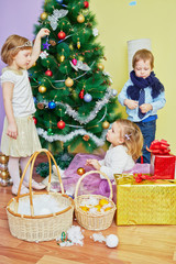 Three children decorate christmas tree, girl hangs blue star