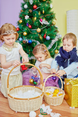 Three children decorate wicker baskets grips by christmas tree