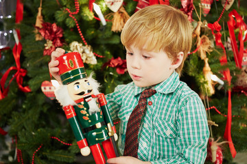 Little boy looks at Nutcracker he holds in his hands