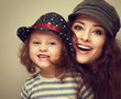 Fashion mother and kid girl toothy laughing in caps. Vintage