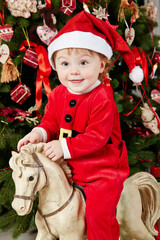 Portrait of little girl dressed in santa suit sitting on horse