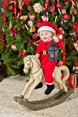 Smiling little girl dressed in santa suit sits on hobby-horse