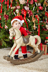 Little girl dressed in santa suit stands with rocking horse