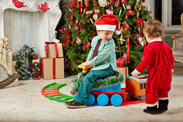Little boy in Santa cap rides toy plastic steam engine at room