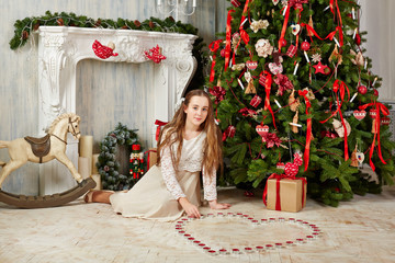 Teenage girl sits on floor under Christmas tree
