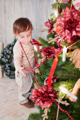 Little girl stands near Christmas tree, looking over